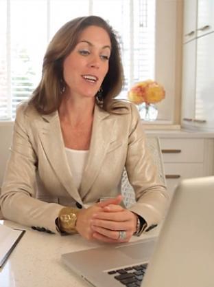 Sarah sitting at desk and looking at computer.