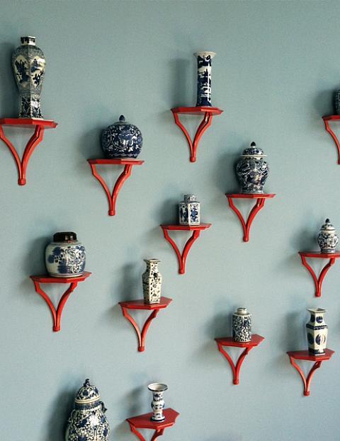 Red sconces holding blue ginger jars